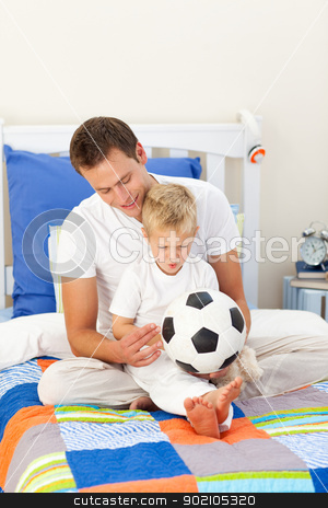 Adorable little boy and his father playing with a soccer ball stock photo, Adorable little boy and his father playing with a soccer ball sitting on bed by Wavebreak Media