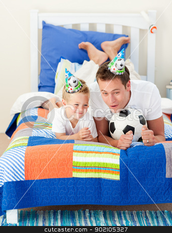 Adorable child and his father playing with a soccer ball stock photo, Adorable child and his father playing with a soccer ball lying on bed by Wavebreak Media