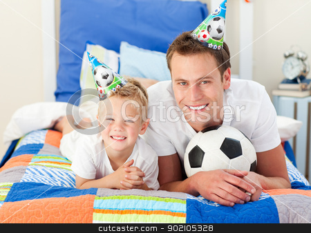 Happy child and his father playing with a soccer ball stock photo, Happy child and his father playing with a soccer ball lying on bed by Wavebreak Media