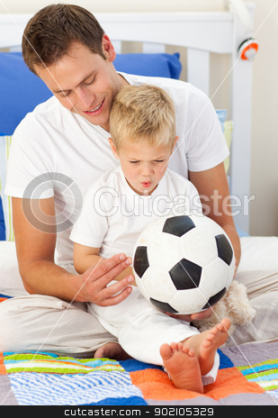 Blond little boy and his father playing with a soccer ball stock photo, Blond little boy and his father playing with a soccer ball sitting on bed by Wavebreak Media