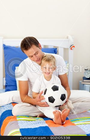Cute little boy and his father playing with a soccer ball stock photo, Cute little boy and his father playing with a soccer ball sitting on bed by Wavebreak Media