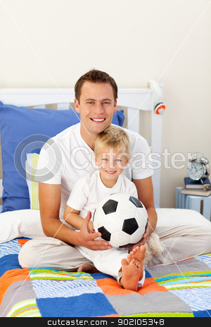 Portrait of a little boy and his father playing with a soccer ba stock photo, Portrait of a little boy and his father playing with a soccer ball sitting on bed by Wavebreak Media