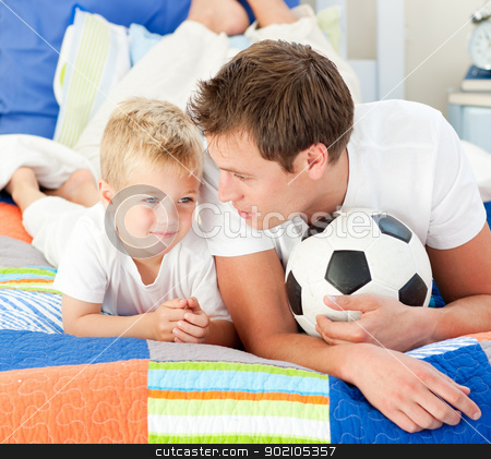 Attentive father and his son playing with a soccer ball  stock photo, Attentive father and his son playing with a soccer ball lying on bed by Wavebreak Media