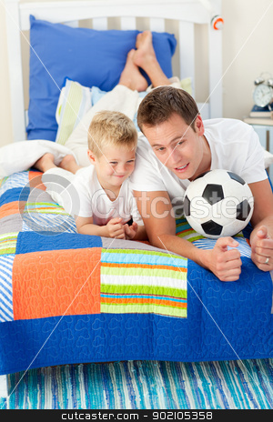 Handsome father and his son playing with a soccer ball stock photo, Handsome father and his son playing with a soccer ball lying on bed by Wavebreak Media