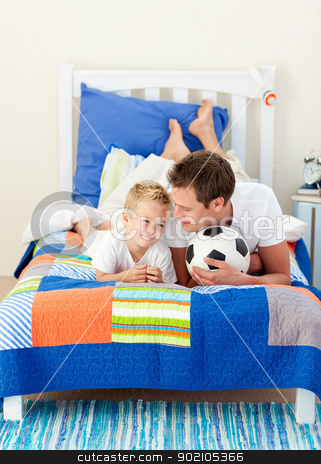Attractive father and his son playing with a soccer ball stock photo, Attractive father and his son playing with a soccer ball lying on bed by Wavebreak Media