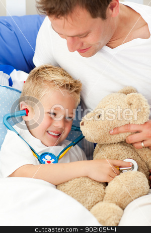 Positive father and his sick son playing with a stethoscope stock photo, Positive father and his sick son playing with a stethoscope sitting on bed by Wavebreak Media