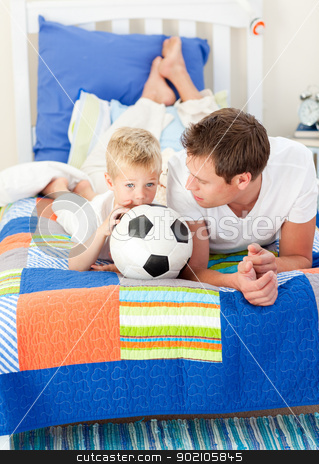 Adorable little boy and his father watching a football match  stock photo, Adorable little boy and his father watching a football match in the kid's bedroom by Wavebreak Media
