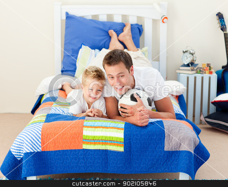 Smiling little boy and his father watching a football match stock photo, Smiling little boy and his father watching a football match in the kid's bedroom by Wavebreak Media