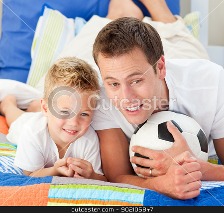 Attentive father and his son watching a football match stock photo, Attentive father and his son watching a football match in the kid's bedroom by Wavebreak Media