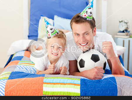 Cute little boy and his father watching a football match stock photo, Cute little boy and his father watching a football match in the kid's bedroom by Wavebreak Media