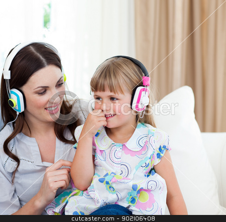 Portrait of a mother and her daughter listening music  stock photo, Portrait of a mother and her daughter listening music on the sofa by Wavebreak Media