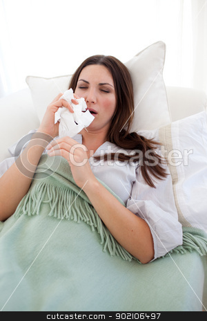 Sick woman blowing lying on the sofa stock photo, Sick woman blowing lying on the sofa at home by Wavebreak Media