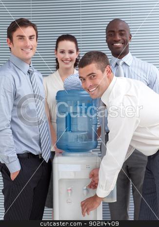 Busines people standing around water cooler stock photo, Busines people standing around water cooler in workplace by Wavebreak Media