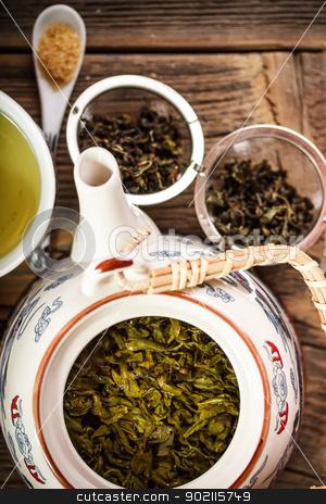 Green tea in teapot stock photo, Green tea in teapot, dry green tea in background by Grafvision