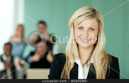 Businesswoman in front of her team in an office stock photo, Businesswoman in front of her team in an office with a green background by Wavebreak Media