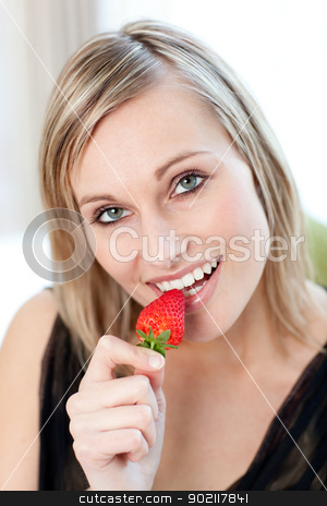 Radiant woman eating a strawberry  stock photo, Portrait of a radiant woman eating a strawberry  by Wavebreak Media