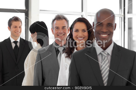 smiling Business man looking at camera with group in background stock photo, Business man looking at camera with group in background by Wavebreak Media