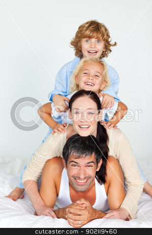 Parents and children playing in bed stock photo, Parents and children playing together in bed by Wavebreak Media