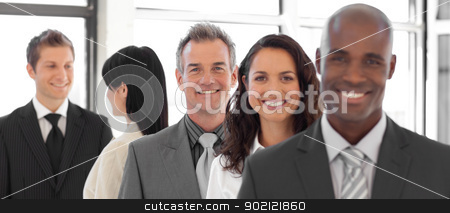 Serious Business man looking at camera with group in background stock photo, Business man looking at camera with group in background by Wavebreak Media