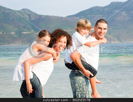 Parents giving two young children piggyback rides stock photo, Parents giving two young children piggyback rides on the beach by Wavebreak Media