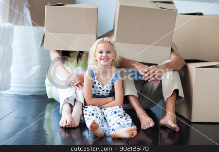 Parents and daughter playing at home with boxes stock photo, Parents and daughter playing with boxes after moving house by Wavebreak Media
