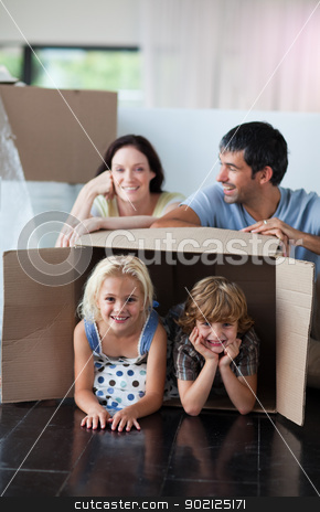 Happy family playing at home with boxes stock photo, Happy family playing with boxes after moving house by Wavebreak Media