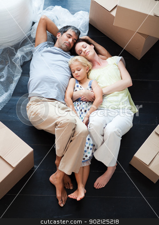 Parents and daughter sleeping on the floor stock photo, Parents and daughter sleeping on the floor of their new house by Wavebreak Media