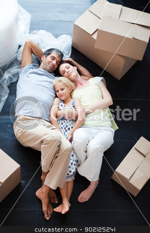 Parents and daughter lying on the floor stock photo, Parents and daughter lying on the floor of their new house by Wavebreak Media
