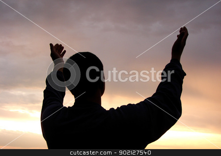 man  stock photo, A man stands on against a sun with heaved up hands                                 by Vitaliy Pakhnyushchyy