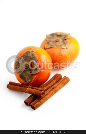 Persimmon Cinnamon stock photo, Closeup of persimmons and cinamon on white background. by Henrik Lehnerer