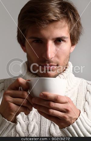 Handsome man in sweater drinking tea stock photo, Handsome and beautiful man in white sweater drinking tea by yekostock