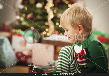 Young Boy Enjoying Christmas Morning Near The Tree stock photo, Cute Young Boy Enjoying Christmas Morning Near The Tree. by Andy Dean