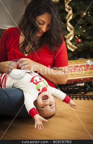 Ethnic Woman With Her Mixed Race Baby Christmas Portrait stock photo, Young Attractive Ethnic Woman With Her Newborn Mixed Race Baby Near The Christmas Tree. by Andy Dean