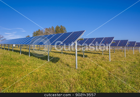 Solar panels stock photo, Solar panels in field with blue sky used to furnish electricity to building by Christian Delbert