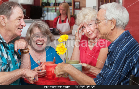 Woman with Friends Holding Head stock photo, Woman holding forehead as friends laugh at the table by Scott Griessel