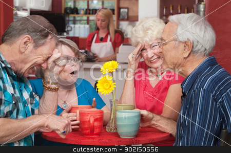 Cringing Lady With Friends stock photo, Woman cringing with group of senior friends in a cafe by Scott Griessel