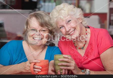 Pair of Smiling Friends stock photo, Two happy senior friends with mugs at table by Scott Griessel