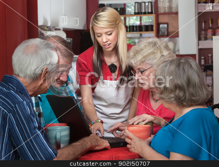 Helpful Waitress with Seniors on Laptop stock photo, Waitress helping senior citizens with computer in coffeehouse by Scott Griessel