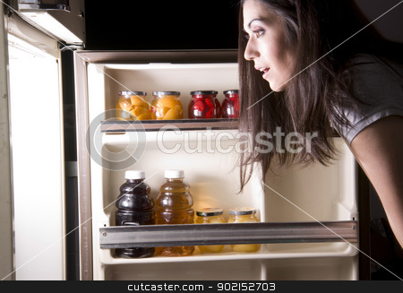 Fridge Raid stock photo, A woman raids the refrigerator late at night by Christopher Boswell