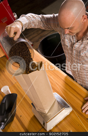 Coffee Packing stock photo, An experienced coffee roaster bags up his finished product. by Christopher Boswell