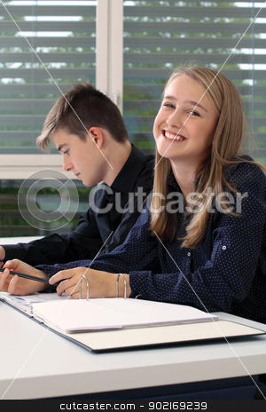 Highschool students working in class stock photo, Photo of two students in their class writing in their notebooks. by © Ron Sumners