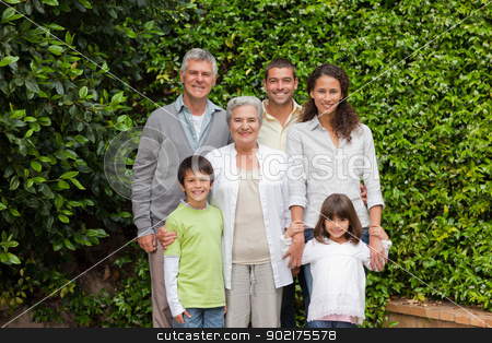 Portrait of a happy family looking at the camera in the garden stock photo, Portrait of a happy family looking at the camera in the garden by Wavebreak Media