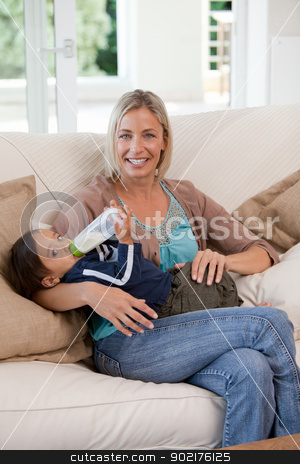 Mother giving a  bottle of milk to her son stock photo, Mother giving a bottle of milk to her son at home by Wavebreak Media