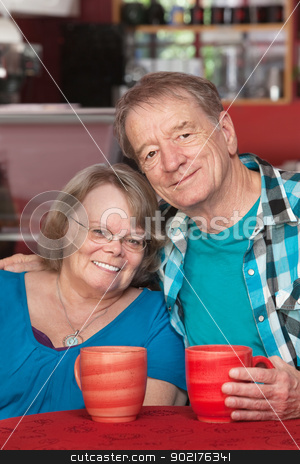 Happy Elderly Couple stock photo, Happy senior man and woman sitting at table with mugs by Scott Griessel