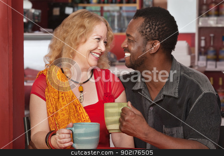 Smiling Mixed Couple Having Coffee stock photo, Smiling mixed couple with drinks in a cafe by Scott Griessel
