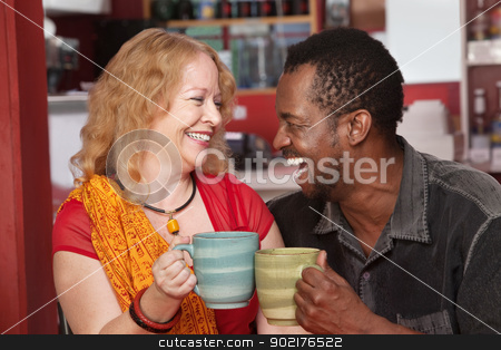 Smiling Mixed Couple Laughing stock photo, Happy Black man and European woman laughing together in cafe by Scott Griessel