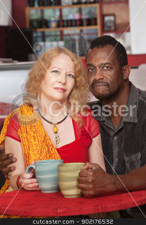 Calm Mixed Couple with Mugs stock photo, Calm black and white couple with mugs in restaurant by Scott Griessel