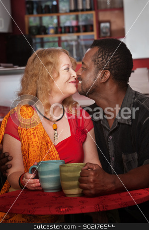 Mixed Eskimo Kiss in Cafe stock photo, Mixed middle aged couple do an Eskimo Kiss in cafe by Scott Griessel