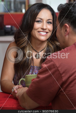 Lovers Holding Hands stock photo, Smiling pretty woman holding hands with friend in bistro by Scott Griessel
