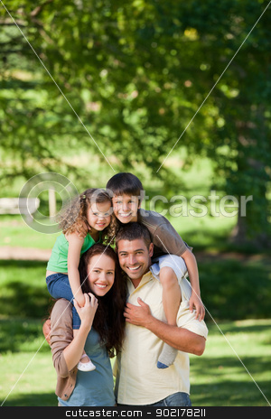 Parents giving children a piggyback stock photo, Parents giving children a piggyback by Wavebreak Media